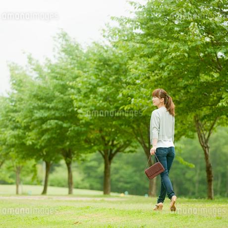 新緑の並木と歩く女性の写真素材 [FYI02056839]