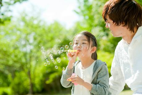 シャボン玉で遊ぶ女の子と父親の写真素材 [FYI02056890]