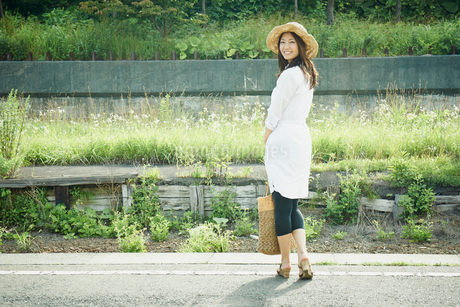 駅のホームで振り返る女性の写真素材 [FYI02056898]