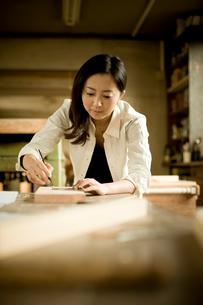木材に印を付ける女性の写真素材 [FYI02056902]