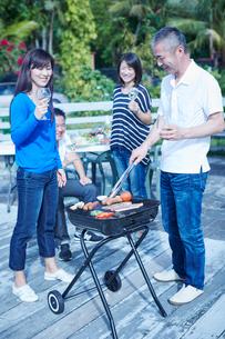 ガーデンパーティーでバーベキューをする2組の夫婦の写真素材 [FYI02056939]