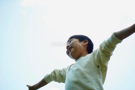 腕を広げる男の子と青空の写真素材 [FYI02056945]