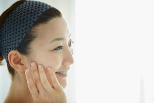 頬に触れる女性の横顔の写真素材 [FYI02056961]