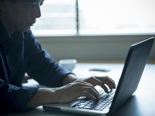 ホームオフィスで仕事をするシニア男性の写真素材 [FYI02057004]