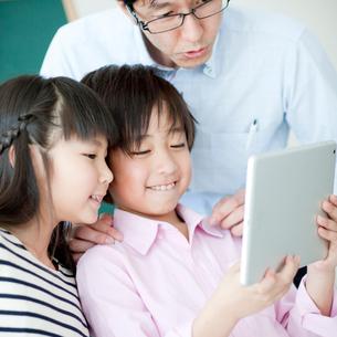 教室でタブレットPCを見る小学生の女の子と男の子と先生の写真素材 [FYI02057046]