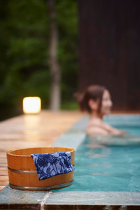 露天風呂の風呂桶と入浴する女性の写真素材 [FYI02057067]