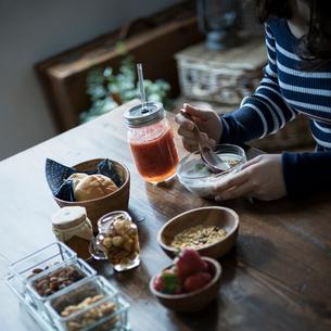 フルーツグラノーラヨーグルトを食べる女性の手元の写真素材 [FYI02057069]