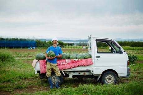 スイカを積んだトラックとスイカを抱える笑顔の農夫の写真素材 [FYI02057084]