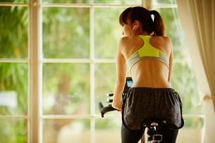 エアロバイクで運動する女性の後ろ姿の写真素材 [FYI02057098]