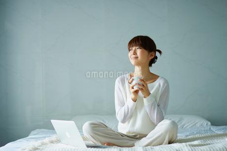 ベッドでコーヒーを飲む女性の写真素材 [FYI02057131]