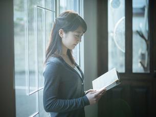 窓辺で本を読む女性の横顔の写真素材 [FYI02057165]