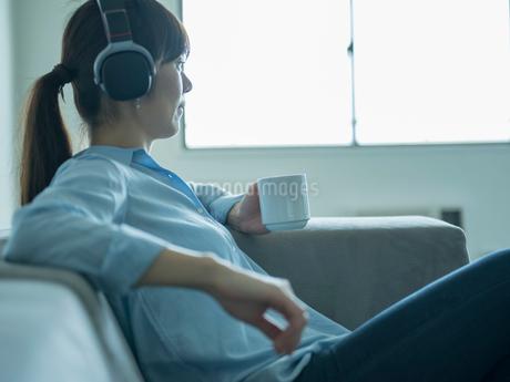 ヘッドフォンをつけてコーヒーカップを持つミドル女性の写真素材 [FYI02057170]