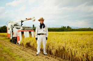 稲田のコンバインと笑顔の農夫の写真素材 [FYI02057172]