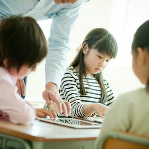 教室で先生と一緒にタブレットPCを操作する小学生の写真素材 [FYI02057179]