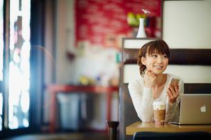 カフェでノートパソコンを開きスマートフォンを持つ女性の写真素材 [FYI02057181]