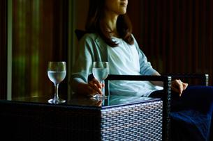 テーブルの上の水が入ったグラスと椅子に座る女性の写真素材 [FYI02057185]