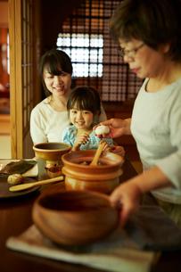 おにぎりを作る三世代女性ファミリーの写真素材 [FYI02057187]