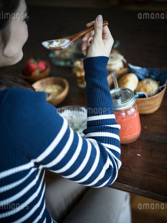 フルーツグラノーラヨーグルトを食べる女性の後ろ姿の写真素材 [FYI02057212]