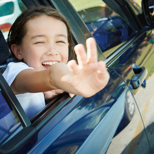車の窓から手を振る女の子の写真素材 [FYI02057229]