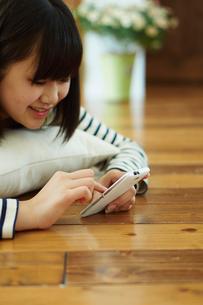 床に寝転びスマートフォンを操作する10代女性の写真素材 [FYI02057238]