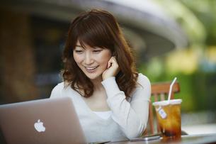 オープンカフェでノートパソコンを見る女性の写真素材 [FYI02057242]