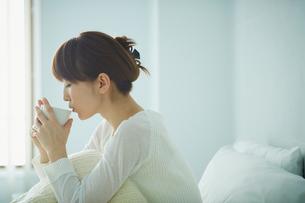 ベッドでコーヒーを飲む女性の写真素材 [FYI02057250]