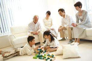 積木で遊ぶ子供達とソファに座る両親と祖父母の写真素材 [FYI02057257]