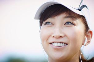 イヤホンをつけランニングキャップを被った笑顔の女性の写真素材 [FYI02057274]