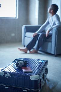 スーツケースとソファに座るミドル男性の写真素材 [FYI02057282]