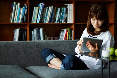 本棚の前でタブレットPCを操作する女性の写真素材 [FYI02057286]