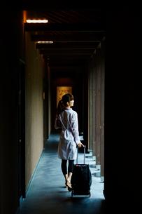 キャリーバッグを引いて歩く女性の後ろ姿の写真素材 [FYI02057290]