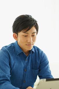 タブレットPCを見る男性の写真素材 [FYI02057294]