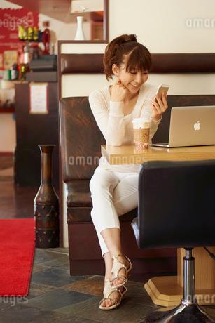 カフェでコーヒーを飲みながらスマートフォンを見る女性の写真素材 [FYI02057295]