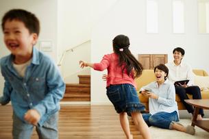リビングルームで走り回る子供達とくつろぐ両親の写真素材 [FYI02057331]