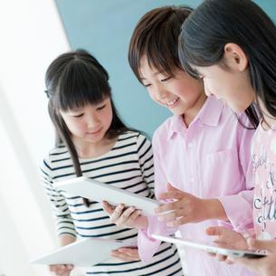 教室でタブレットPCを操作する小学生3人の写真素材 [FYI02057354]