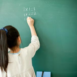 黒板で算数の問題を解く小学生の女の子の写真素材 [FYI02057382]