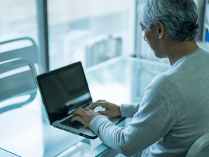 ノートパソコンを操作するシニア男性の写真素材 [FYI02057397]