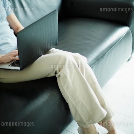 ソファに座りノートパソコンを操作する女性の写真素材 [FYI02057461]