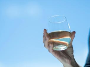 白ワインが入ったグラスを持つ女性の手の写真素材 [FYI02057494]