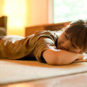 床に寝転ぶ女性の写真素材 [FYI02057499]
