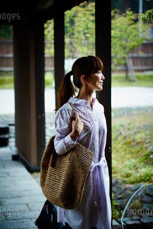 バッグを持ちエントランスを歩く女性の写真素材 [FYI02057513]