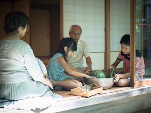 縁側でスイカや野菜を冷やす祖父母と孫たちの写真素材 [FYI02057514]