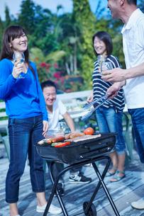 ガーデンパーティーでバーベキューをする2組の夫婦の写真素材 [FYI02057530]