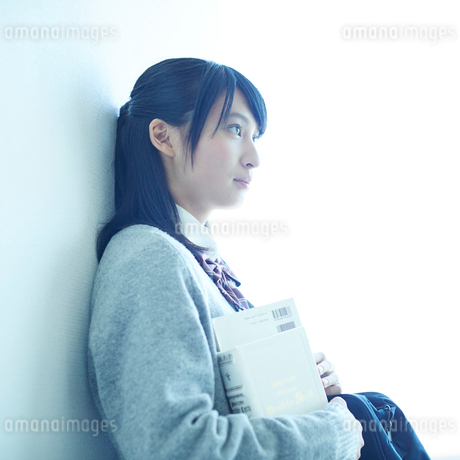 壁に寄りかかる女子学生の横顔の写真素材 [FYI02057541]