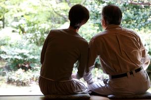 縁側から庭を眺めるシニア夫婦の写真素材 [FYI02057543]