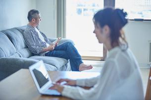 ノートパソコンを操作する女性と読書をする男性の写真素材 [FYI02057548]