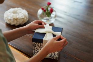 ギフトボックスにリボンを結ぶ女性の手元の写真素材 [FYI02057562]