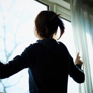 カーテンを開ける女性の写真素材 [FYI02057590]
