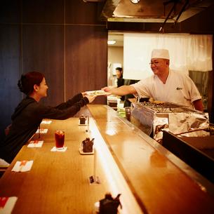 料理を受け渡しする料理人と女性客の写真素材 [FYI02057598]