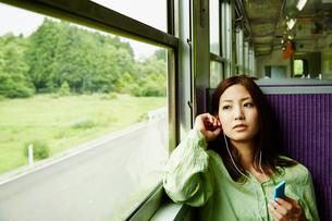 列車の中で音楽を聴く女性の写真素材 [FYI02057622]